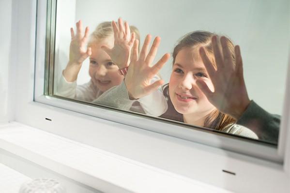 Zwei Kinder blicken durch ein Kellerfenster